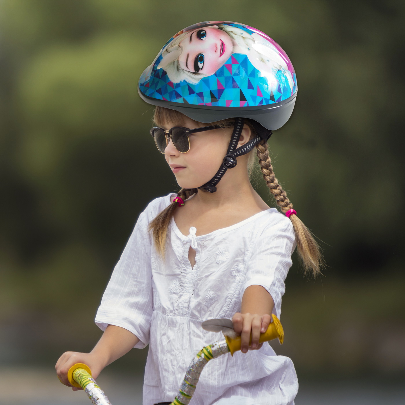 Close-up portrait of proud pretty young girl in white clothing, sunglasses with long blond braids wearing pink safety helmet riding child bicycle on blurred green trees summer copy space background.