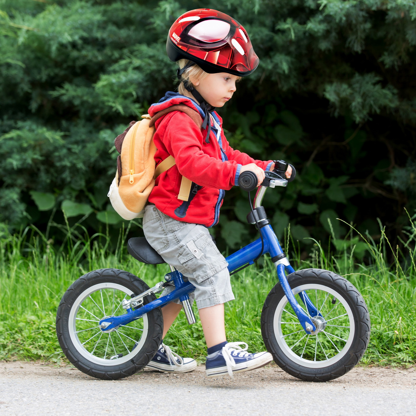 Cute toddler boy with blue helmet, riding balance bike on the street