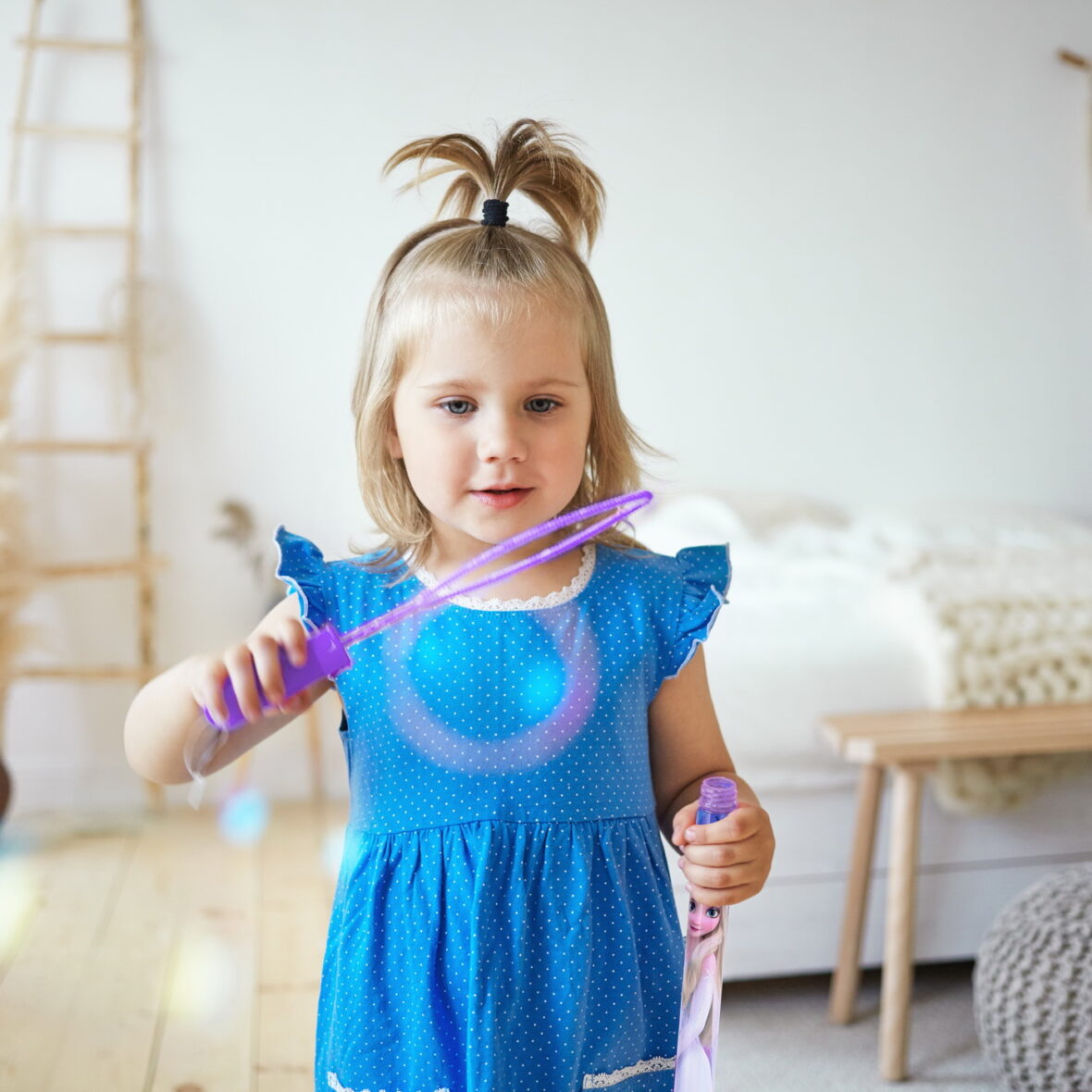 Happy beautiful female kid with ponytail having fun indoors, blowing soap bubbles in parents bedroom. Charming little girl wearing cute blue dress entertaining herself, playing at home alone